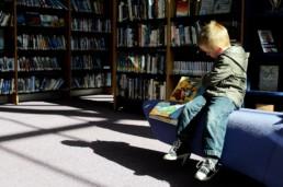 Junge liest Buch in einer Bibliothek